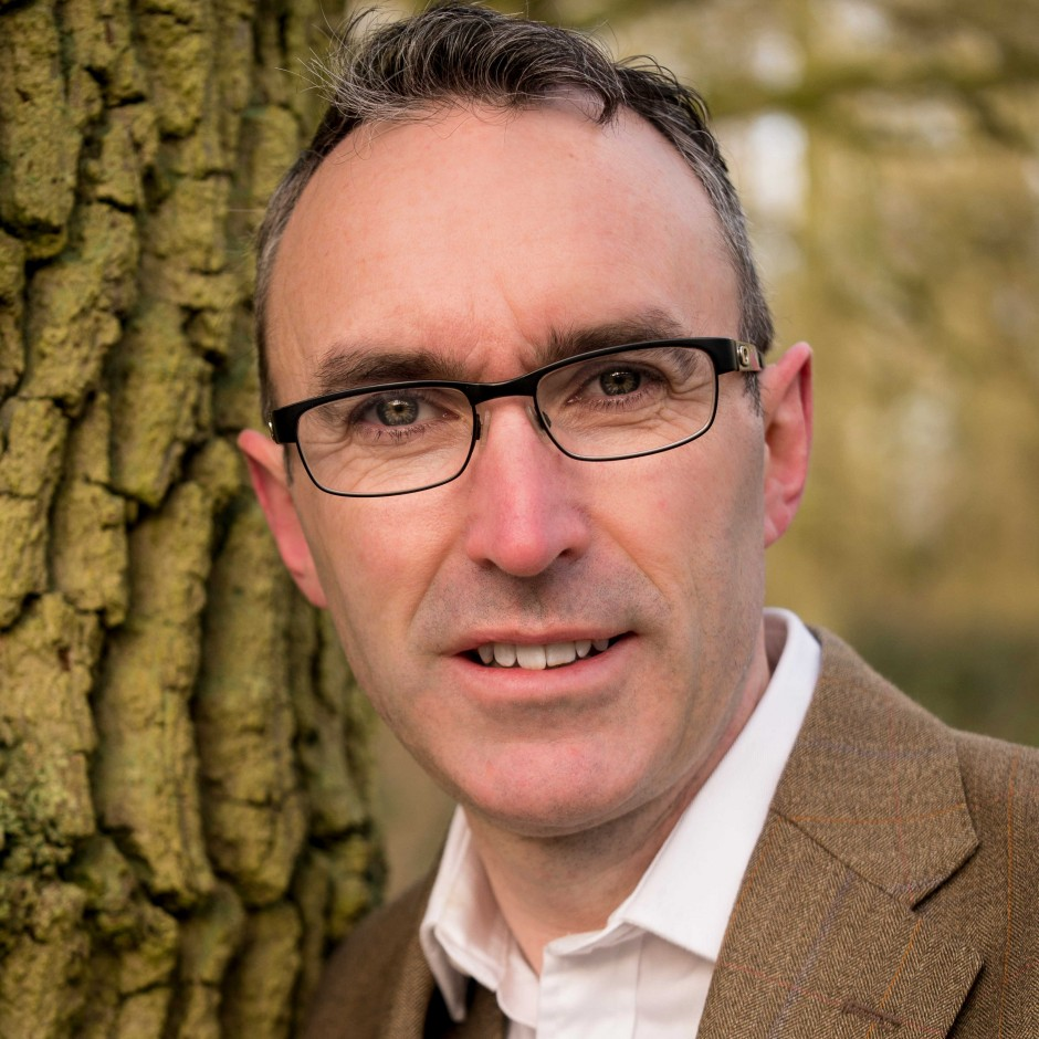 A headshot of silvologist and writer Gabriel Hemery, standing in front of a tree trunk