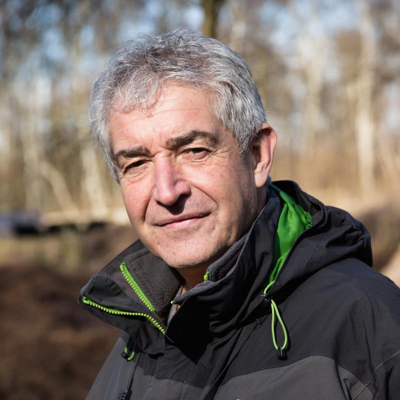 Head and shoulders shot of Tony Juniper outside, wearing a grey and green hooded jacket
